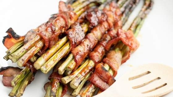 Bacon wrapped asparagus on a white plate with a wooden spoon