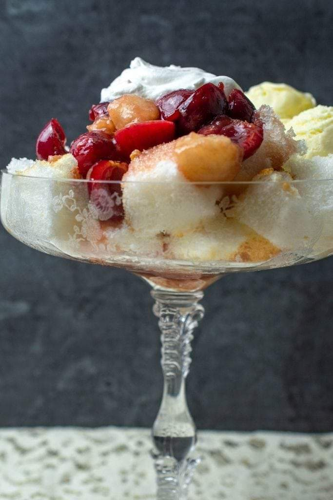 A cherry and peach trifle served in a crystal champagne saucer on a lace cloth.