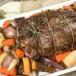 Stuffed Beef tenderloin on a platter with roasted root vegetables.
