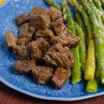A blue plate filled with honey garlic steak bites and asparagus.
